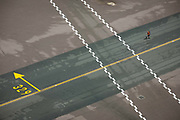 High aerial view (from control tower) of Heathrow airport aviation markings on concrete landscape. A ramp agent walks over directional lines that help pilots navigate to specific locations around the airport of five terminals on a site that covers 12.14 square kilometres (4.69 sq mi). London Heathrow is a major international airport, the busiest airport in the United Kingdom and the busiest airport in Europe by passenger traffic. It is also the third busiest airport in the world by total passenger traffic, handling more international passengers than any other airport around the globe.