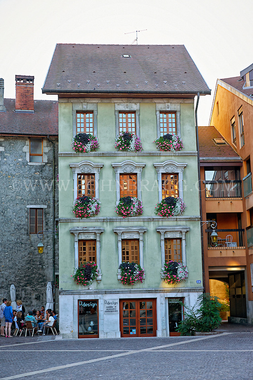 View of a gorgeous, green,  Neo-Classic building, and a cobblestone walkway, Old Town Annecy, France.