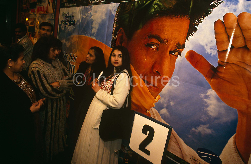 On a night out with friends, a group of five ladies are queuing for screen 2 in a Croydon cinema, South  London to see a Bollywood romantic film. On a poster behind, a giant movie hero's face looks towards the viewer with a hand raised in a salute. The man is of a dashing, handsome character  whose dark skin looks like a tanned European person. The women are in good spirits before their favourite film and gather together in the cinema's foyer in expectation. One lady is dressed in a long, smart dress and is staring with wide open eyes. She has a large handbag over the left shoulder and her long hair is spilling down her back.<br /> <br /> .