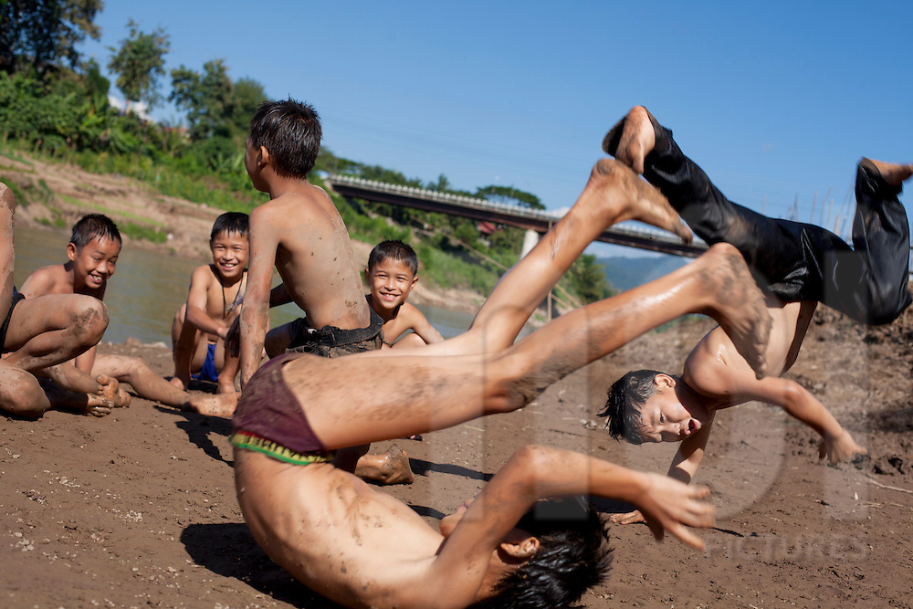 Kids are playing and dancing hip hop along the Nam Khan river on a sunny day. Luang Prabang, Laos, Asia