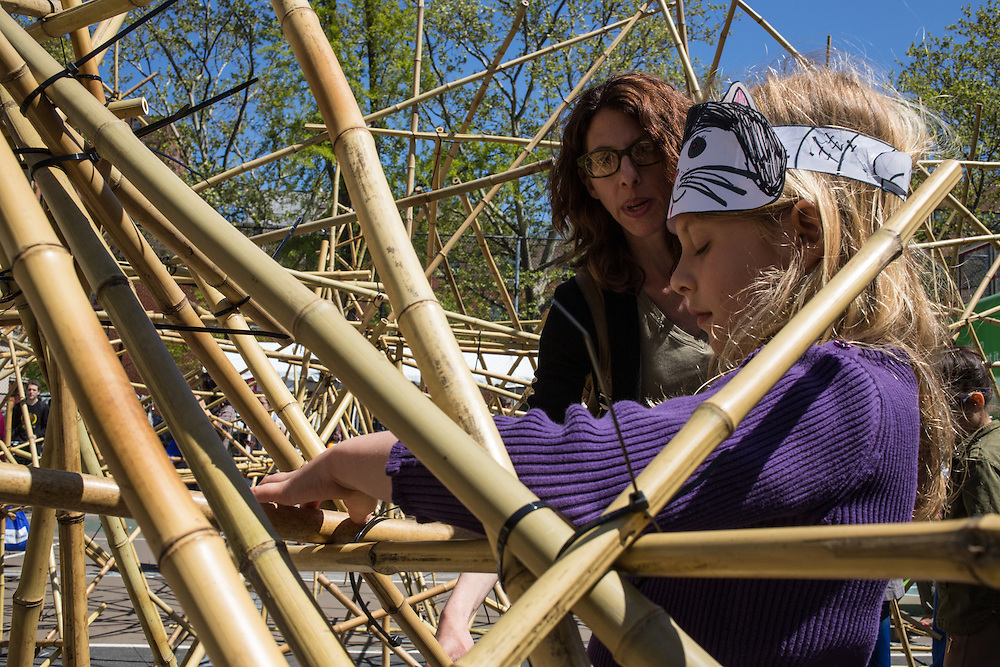 A girl fastens a piece of bamboo to a structure at Sub Rosa's Sustanable Play exhibit as her mother watches and gives advice.