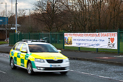 "© Licensed to London News Pictures . 19/01/2018 . Manchester , UK . An ambulance is driven past a banner hung from railings in front of The Church of Jesus Christ of Latter-day Saints on the A560 Altrincham Road in Wythenshawe which references Salman Abedi's murderous terror attack on the Manchester Arena with the use of a photograph from the scene of the attack , alongside the words "" Are you prepared for possible disaster "" and the logo of the I Love Mcr charity . The banner features an invitation to visit the church "" To see if we can help"" . Photo credit : Joel Goodman/LNP"