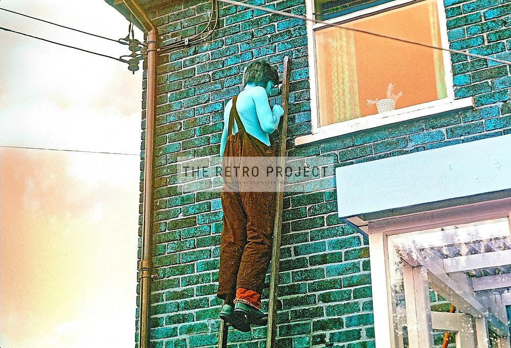 Vintage Man on Ladder colourised monochrome grainy photo