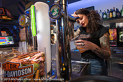 Bartender Giada Causio at a party at the Sidestand Cafe in the Harley-Davidson dealership in Pavia during EICMA, the largest international motorcycle exhibition in the world. Milan, Italy. November 19, 2015.  Photography ©2015 Michael Lichter.