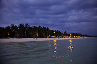 Early evening views with dramatic cloudy skies across the bay to White Sand Beach, Boracay, Philippines.
