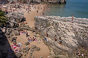 Sunbathers lie surrounded by rocks on the beach in mid-day heat, on 12th July 2016, at Cascais, near Lisbon, Portugal. Cascais is a coastal town and a municipality in Portugal, 30 kilometres 19 miles west of Lisbon. The former fishing village gained fame as a resort for Portugals royal family in the late 19th century and early 20th century. Nowadays, it is a popular vacation spot for both Portuguese and foreign tourists and located on the Estoril Coast also known as the Portuguese Riviera.