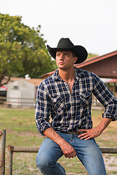 handsome cowboy sitting on a gate by a ranch