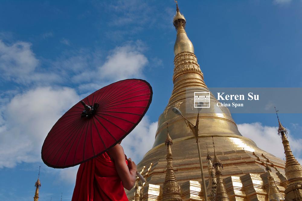 Monk with red umbrella with Shwedagon Pagoda, Yangon, Myanmar