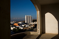 """The development of one of the rich neighborhoods is seen through the windo of an unfinished """"narco mansion"""" in  Culiacan.  In these neighborhoods the houses are big and often come with security guards and barbed wire fence.  Many say that drug money is laundered through real estate development."""