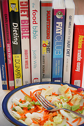 Discarded plate of salad beside various dieting books,