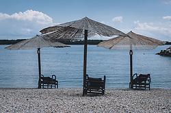 THEMENBILD - Strandliegen und Sonnenschirme aus Schilfrohr auf einem Kieselstrand, aufgenommen am 03. Juli 2020 in Novigrad, Kroatien // Beach chairs and umbrellas made of shield cane on a pebble beach, in Novigrad, Croatia on 2020/07/03. EXPA Pictures © 2020, PhotoCredit: EXPA/ Stefanie Oberhauser