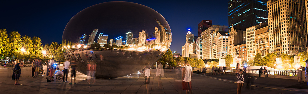 Cloud Gate, a bean-shaped sculpture, is visited by picture taking tourists in the middle of Millennium Park in Chicago.