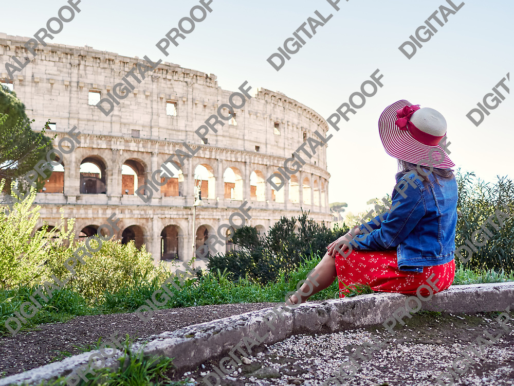 Side view of anonymous stylish woman sitting alone and dreaming on background of beautiful Coliseum in Rome.