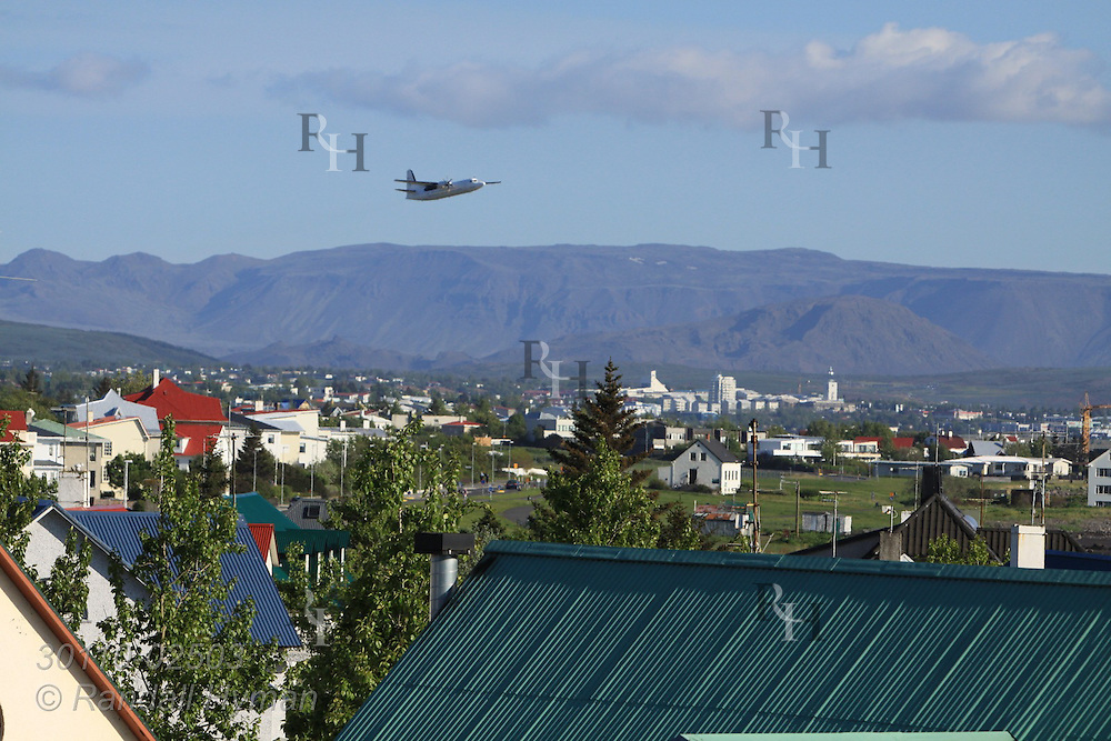 Commercial airplane takes off over rooftops of the western suburbs of Reykjavik, Iceland.