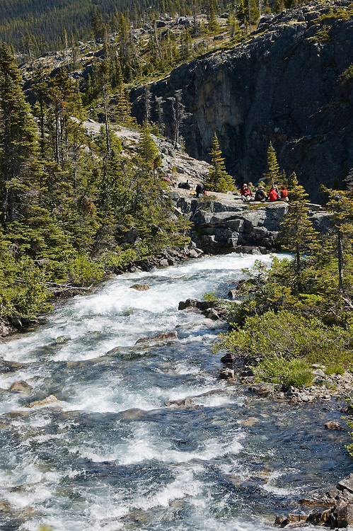 Colorful backpackers stop for lunch along a roaring stream on the Chilkoot Trail.