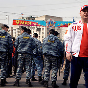 """A man in """"Russia"""" jacket stands in front of riot police guarding a demonstration by Communist supporters on Labour Day."""