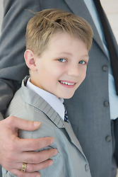 Boy smiling beside father, close up