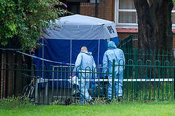 © Licensed to London News Pictures. 04/07/2020. London, UK. Investigators walk towards a forensic tent on Westbourne Estate in Islington. Metropolitan Police Service officers were called at 15:20BST on Saturday, 4 July to Roman Way N7 following reports of shots fired. Officers attended with London Ambulance Service (LAS) and found a man, believed to be aged in his early 20s, suffering from gunshot injuries. Despite their best efforts, he was pronounced dead at the scene. Photo credit: Peter Manning/LNP