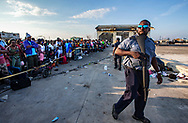Royal Bahamas Defense Force officer maintains order as evacuees wait for transportation to leave Marsh Harbour Port  on Abaco Island on Saturday, September 7, 2019.