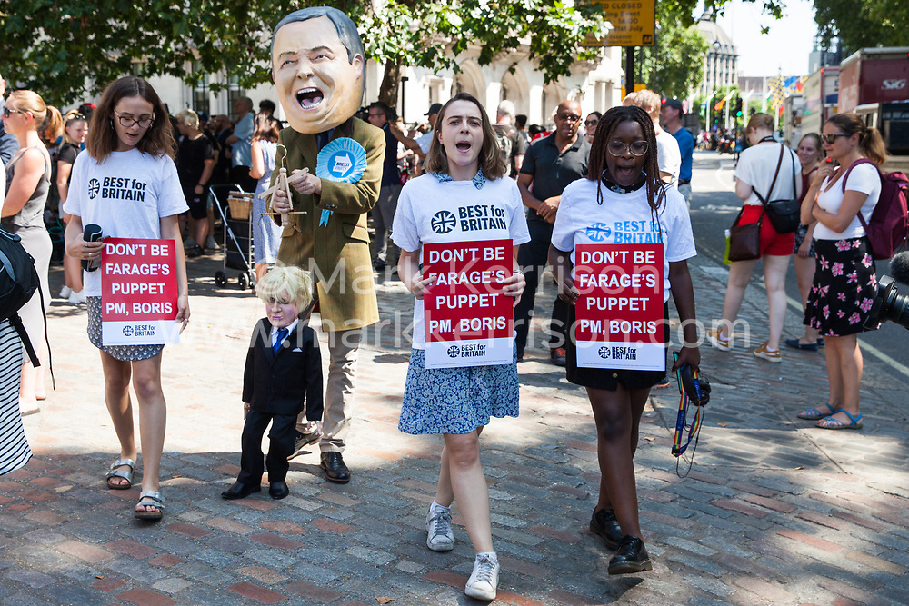 London, UK. 23 July, 2019. Campaigners from Best for Britain protest outside the Queen Elizabeth II Centre with props depicting Boris Johnson as a puppet of Brexit Party leader Nigel Farage prior to the announcement inside the venue that Boris Johnson had been elected as leader of the Conservative Party and would replace Theresa May as Prime Minister.