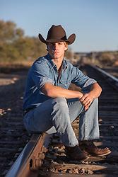 cowboy sitting on railroad tracks