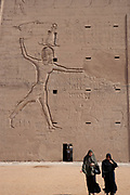 Egyptian women in black attire walking in front of the Edfu Temple
