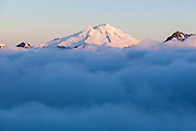 Mount Baker rises above low clouds, as seen from Damnation Peak, North Cascades National Park, Washington.