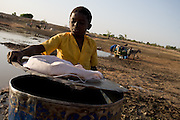 A boy sets up a mesh filter on top a large barrel before filling it with water at the Dikunani dam in Savelugu, northern Ghana, on Friday March 9, 2007. The only of four water sources that has not completely dried out around Savelugu, the pond is used by hundreds of people daily who sometimes walk several kilometers to fetch water. Despite the presence of mesh filters available to people who come get water, cases of guinea worm in the area have gone up sharply in the recent months.