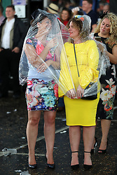 Female racegoers shelter from the rain on Ladies Day during the 2017 Investec Epsom Derby Festival at Epsom Racecourse, Epsom.