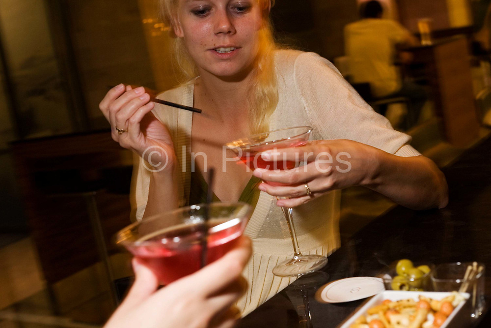 """A young lady from the US finishes stirring her vodka and cranberry juice cocktail and is about to sip her expensive drink at the bar of the Sphere Bar at Heathow Airport's Sofitel Hotel at Terminal 5. Drinking with an unseen friend whose hand we see in the lower part of the picture, the girl raises her conical glass to sip the alcoholic beverage before proposing a toast to their unforeseen night's stay in this luxury hotel after a cancelled flight. Some nuts are on a small dish which are largely untouched. From writer Alain de Botton's book project """"A Week at the Airport: A Heathrow Diary"""" (2009)."""