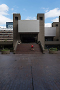 A girl in a red jumper walking up some steps at the Barbican Centre on the 12th September 2019 in London in the United Kingdom. The Barbican Centre is a performing arts centre in the Barbican Estate of the City of London and the largest of its kind in Europe.