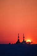 Alaska. North Slope. The sunset backlights oil derricks.