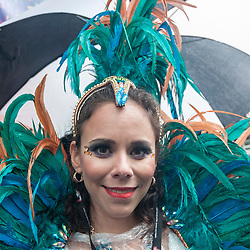 © Licensed to London News Pictures. 31/08/2015. London, UK. A dancer shelters under an umbrella as revellers and dancers brave the heavy rain to take part in Notting Hill Carnival, Europe's biggest Caribbean festival. Photo credit : Stephen Chung/LNP