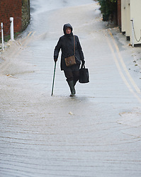 © Licensed to London News Pictures. 25/11/2012..North East England..A woman walks down a flooded side street in Loftus in North Yorkshire following heavy overnight rain that caused traffic disruption and flooding in parts of Cleveland and North Yorkshire...Photo credit : Ian Forsyth/LNP