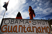 Protest at Parliament Square calling Obama to shut Guantanamo Bay. Men dressed in orange jump suits and wearing black hoods over their heads demonstrate this anti American stance.