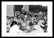 President John F. Kennedy is mobbed by well-wishers and photographers at a garden party at áras an Uachtaráin.<br />
