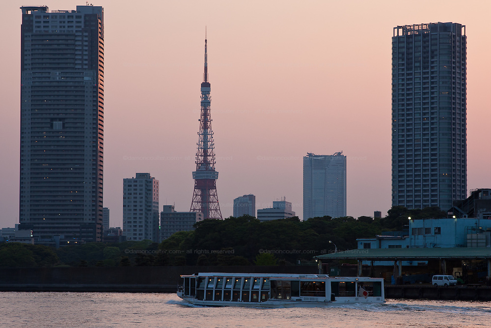 Tokyo Tower and Roppongi Hills from near Kachidooki Bridge with a Tokyo water cruiser pleasure boat sailing past. Tokyo, Japan, Thursday, April 30th 2009