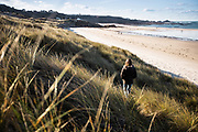 Woman walking through the sand dunes from Le Braye towards Le Carriere beach in low winter sunlight, St Ouen's Bay, Jersey, CI