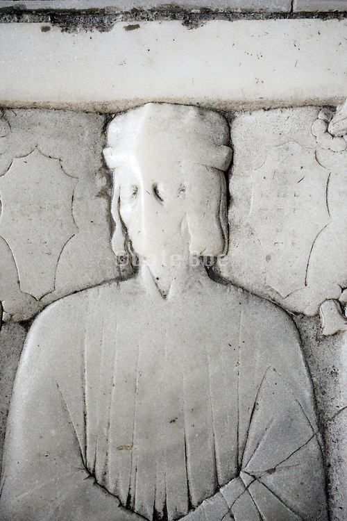 deterirorated walked over medieval tombstone on grave inside church
