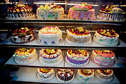 Patisserie of the most colourful type in a shop window. The cakes are elegantly or boldly iced and decorated. London.