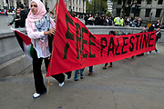 Rally organised by Stop the War coalition  in Trafalgar Square to mark 10 years of war in Afghanistan. A group of women carry a very long banner saying 'Free Palestine'.