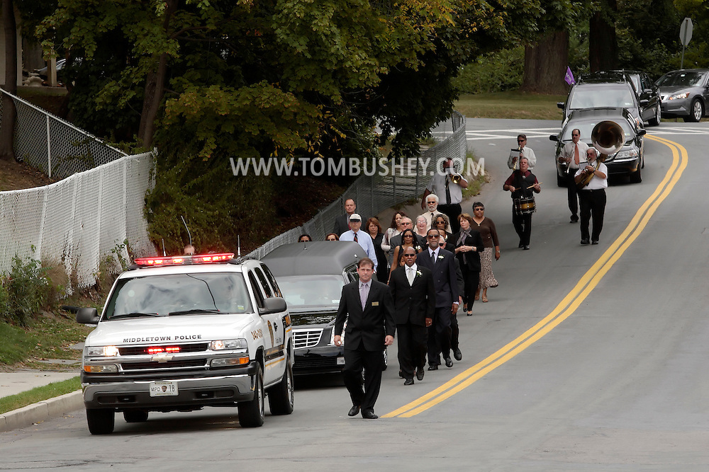 Middletown, New York -  Mourners walk alongside the hearse and are followed by a Dixieland band in the funeral procession for Willie Carter on West Main Street  Sept. 8, 2010.