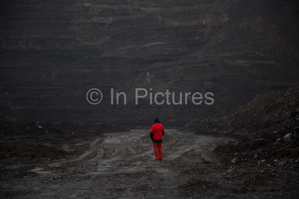 . Hundreds of environmental activists stopping the open cast coal mine Ffos-y-Fran near Merthyr Tydfil, Wales from operating May 3rd 2016. A man in red stares at the black and bleak landscape in front of him in the mine The activists from Reclaim the Power wants the mine shut down and a moratorium on all future open coal mining in Wales. The group Reclaim the Power had set up camp near by and had over three days prepared the action and up to 300 activists all dressed in red went into the mine in the early morning. The activist were plit in three groups and carried various props signifying the red line in the sand, initially drawn in Paris at the COP21. The mine is one of the largest open cast coal mines in the UK and is run by Miller Argent who have to date extracted 5million tons of coal. The activists entered the mine unchallenged by any security or police and the protest went on peacefully till mid afternoon with no arrests made.  Open coal mining is hugely damaging to the local environment and  contributing to global climate change.