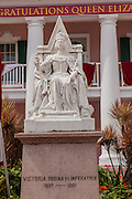 Statue of Queen Victoria in front of the Pink Senate Building in Parliament Square decorated for the Queen's 60th Jubilee in Nassau , Bahamas.