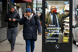© Licensed to London News Pictures. 02/03/2021. London, UK. People without wearing face coverings walk past the government's 'Every covered face is making a difference' awareness poster in north London. The number of Covid-19 infection rate and deaths have dropped more than a quarter within a week as the effect of lockdown restrictions and vaccine rollout is making an impact. Six cases of the P1 variant have been identified in people who recently returned from Brazil. Photo credit: Dinendra Haria/LNP