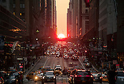 The sunset phenomenon known as Manhattanhenge, when the setting sun aligns with the grid pattern of the city's streets, setting behind 42nd Street, Manhattan, New York City.