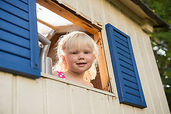 Smiling little girl looking out of tree house