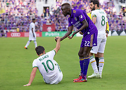 April 8, 2018 - Orlando, FL, U.S. - ORLANDO, FL - APRIL 08: Orlando City defender Lamine Sane (22) helps Portland Timbers midfielder Sebastian Blanco (10) up during the MLS soccer match between the Orlando City FC and the Portland Timbers at Orlando City SC on April 8, 2018 at Orlando City Stadium in Orlando, FL. (Photo by Andrew Bershaw/Icon Sportswire) (Credit Image: © Andrew Bershaw/Icon SMI via ZUMA Press)