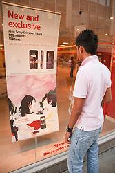 Teenage boy looking at mobile phone advert.