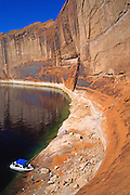 Moor a motorboat and climb steep sandstone to Three Roof Ruin, located 14 miles up the Escalante River Arm of Lake Powell, in Glen Canyon National Recreation Area, Utah, USA.